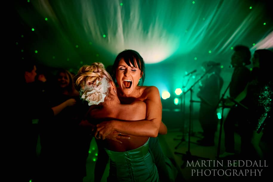 Bride is hugged by her sister during the dancing