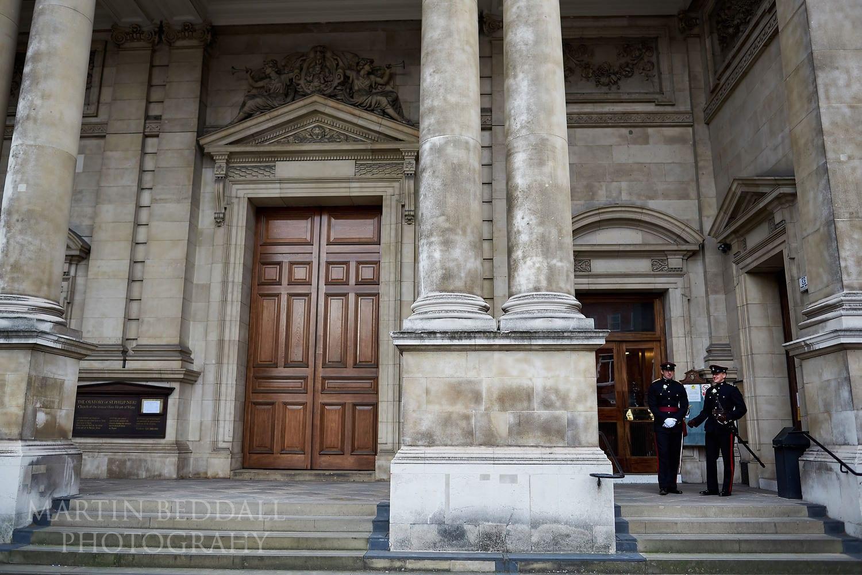Groom and best man in dress uniform wait outside Brompton Oratory