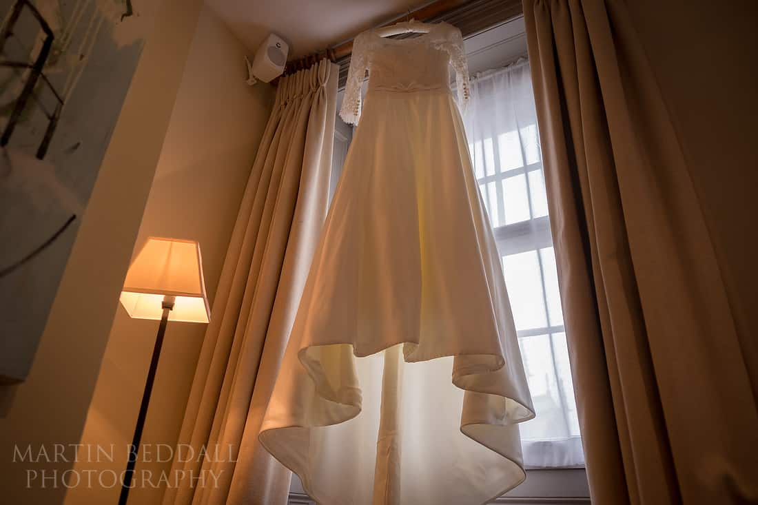 Bride's dress hangs in the window