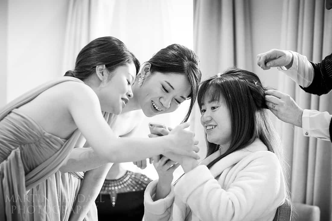 Bridesmaids show bride a photo on a phone