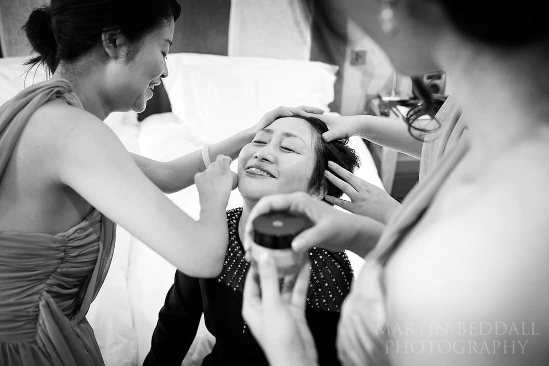 Bridesmaids help bride's mother with her makeup