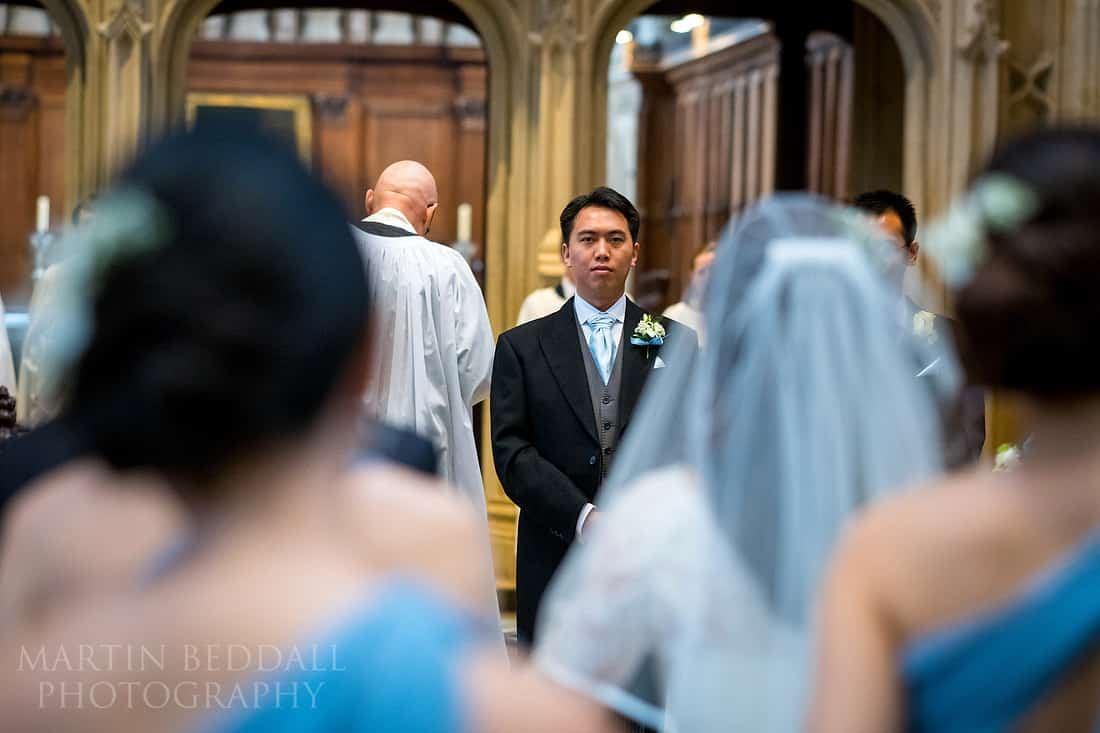 Groom watched the bride walk down the church aisle
