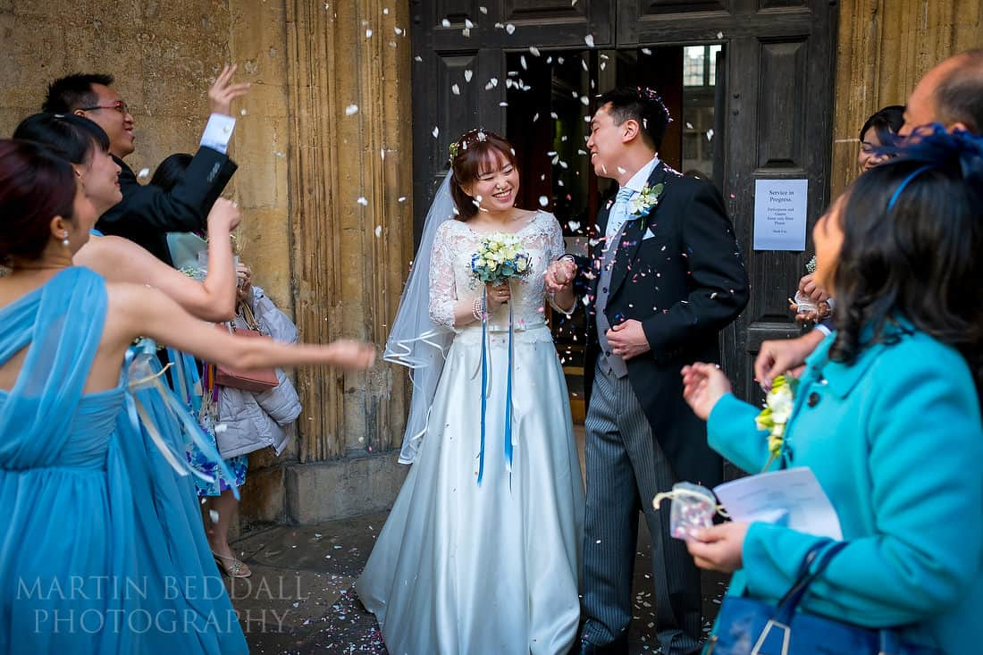 Bride and groom showered in confetti oustide the church