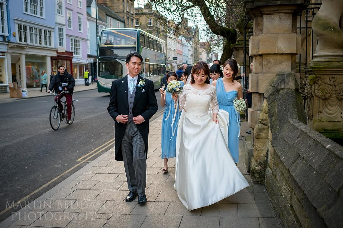 Bride and groom walk down the high street