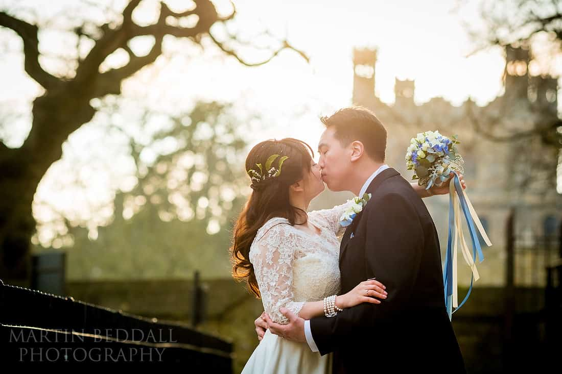 Oxford bride and groom kiss as the sun dips