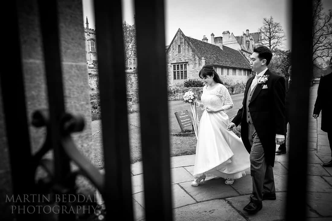Bride and groom wlaking seen through railings