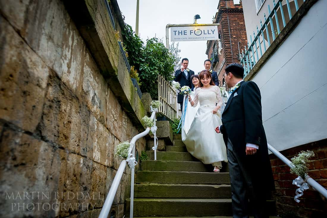 Bridal party walking down steps to the Folly restaurant