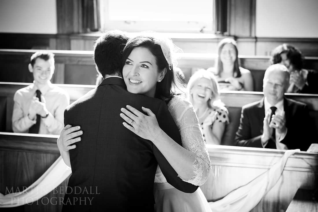 Bride and groom hug in wedding ceremony at Worthing Town Hall