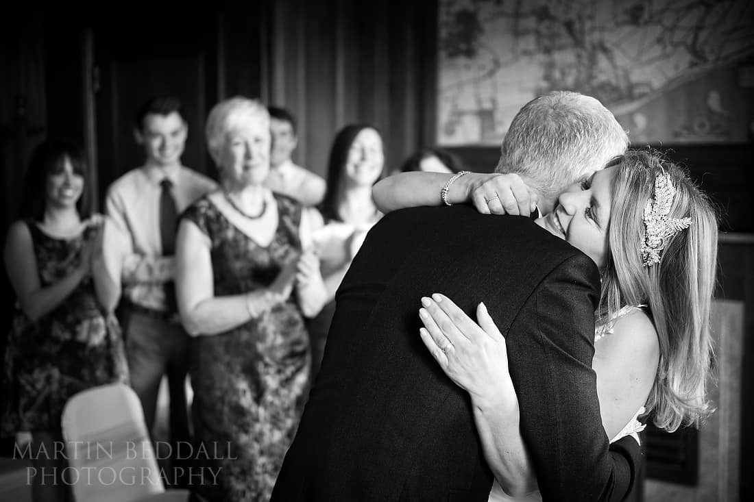 Bride and groom hug at ceremony in Worthing Mayor's parlour