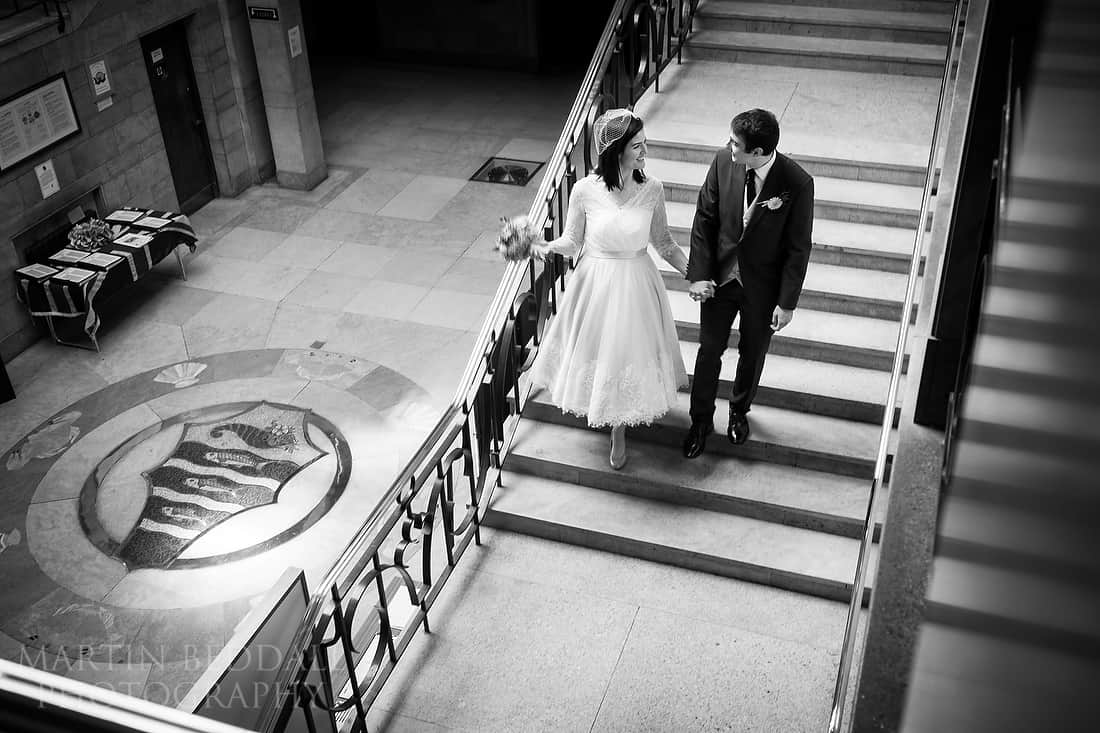 Bride and groom walk hand in hand in the town hall
