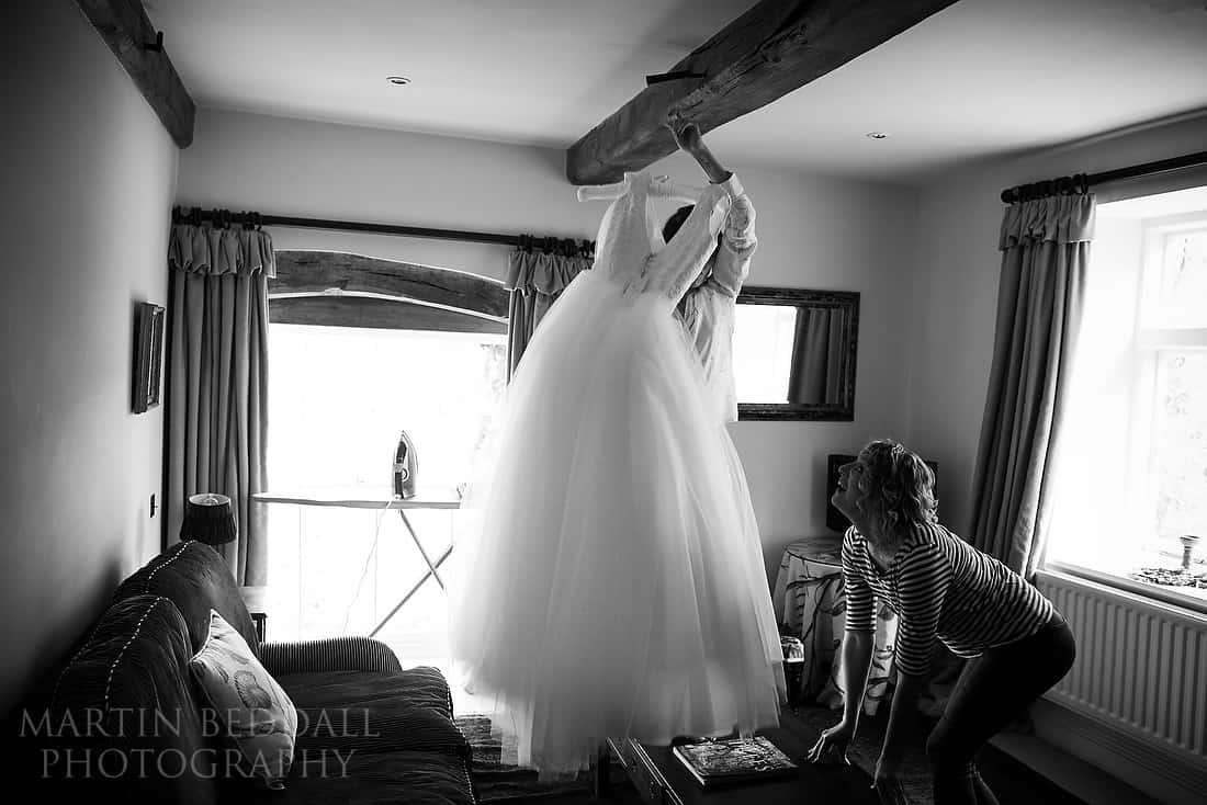 bride hangs up her wedding dress
