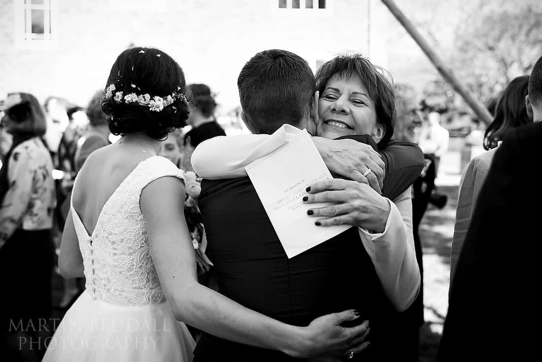 bride's mother hugs the groom