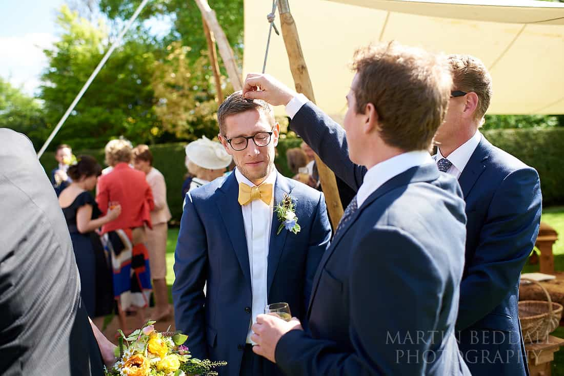 picking confetti out of the groom's hair