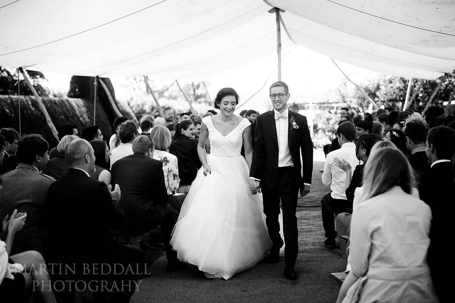 Bride and groom walk back down the aisle at Dewsall Court Wedding