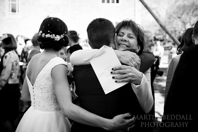 Bride's mother hugs the groom