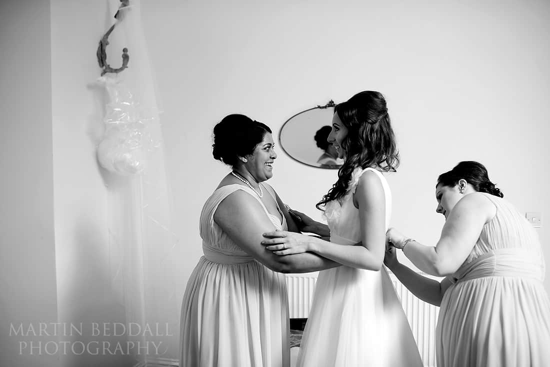 bride gets into the wedding dress with bridesmaids help
