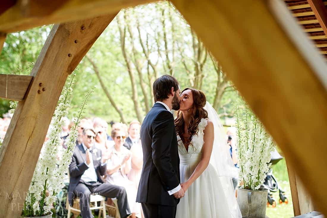 bride and groom kiss at outdoor wedding ceremony at Millbridge Court