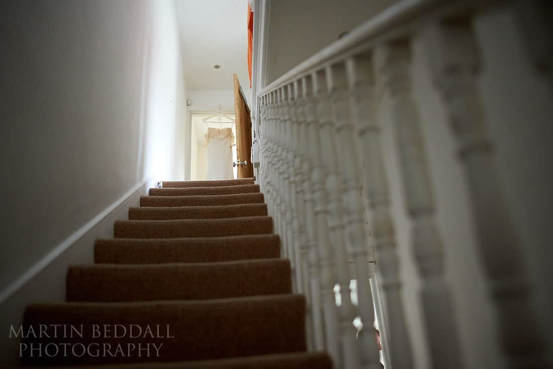 wedding dress hanging at the top of the stairs