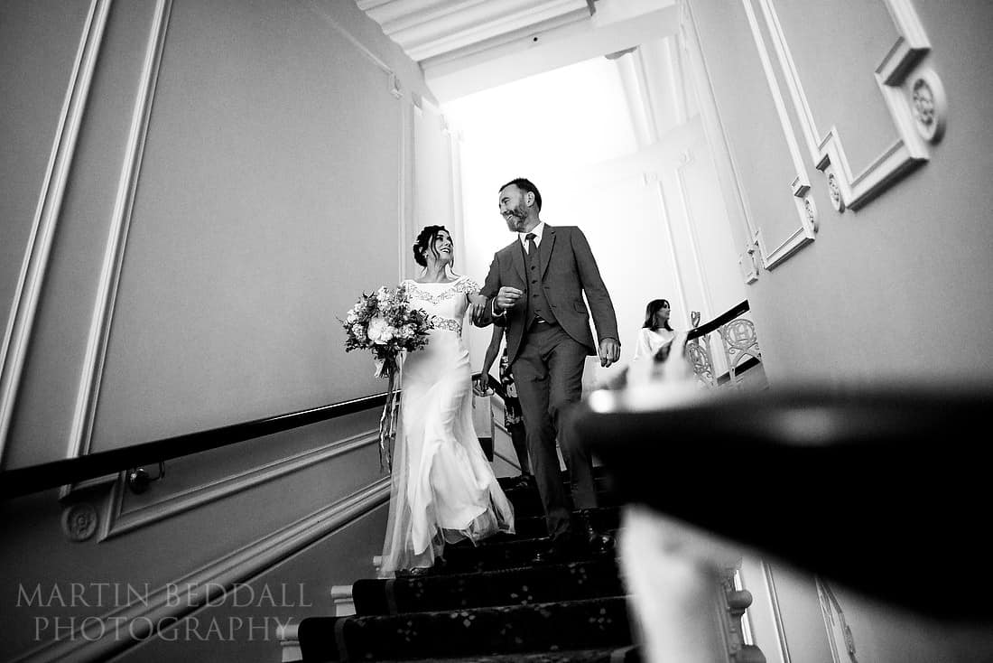 Bride and her father walk down the stairs at the Langham hotel