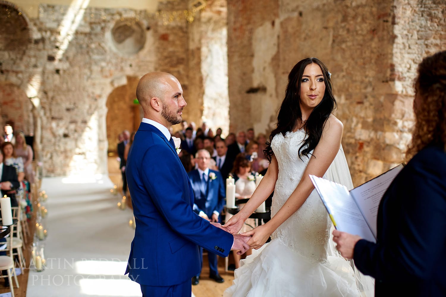 Holding hands during a Lulworth Castle wedding ceremony