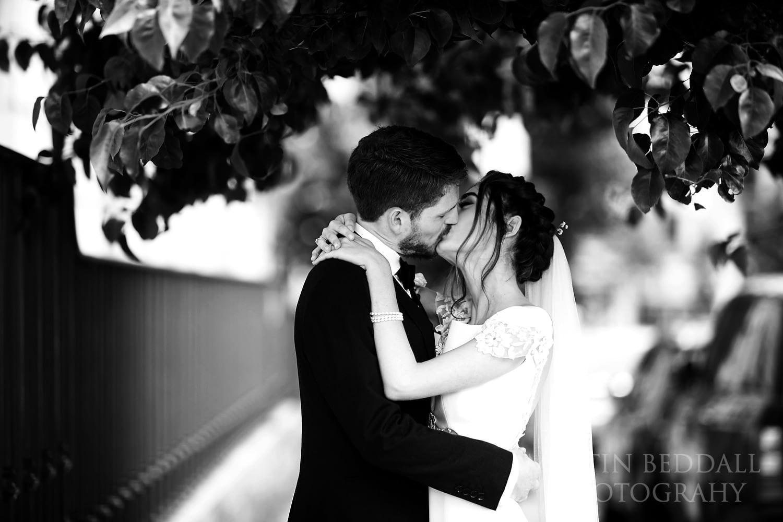 Bride and groom kiss on the street outside RIBA