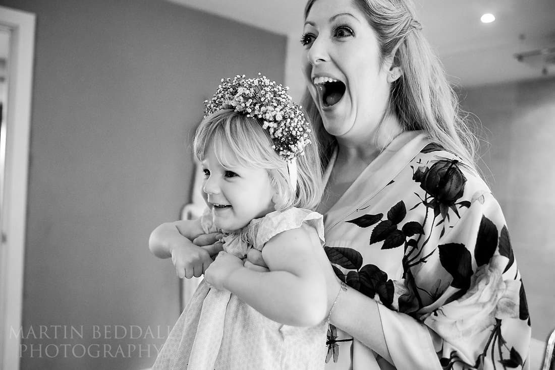 bride holds up the flower girl