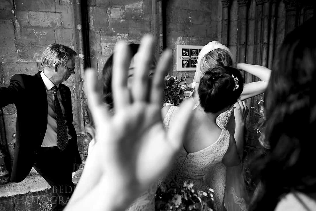 Bridesmaid tries to cover the camera lens