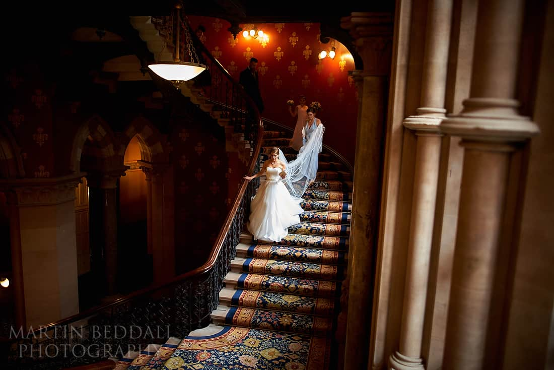 Bride walks down the staircase at St Pancras hotel in London