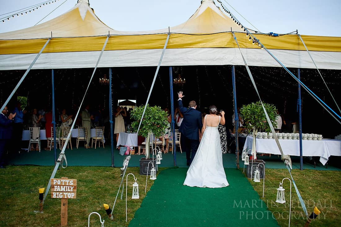 bride and groom enter the big top