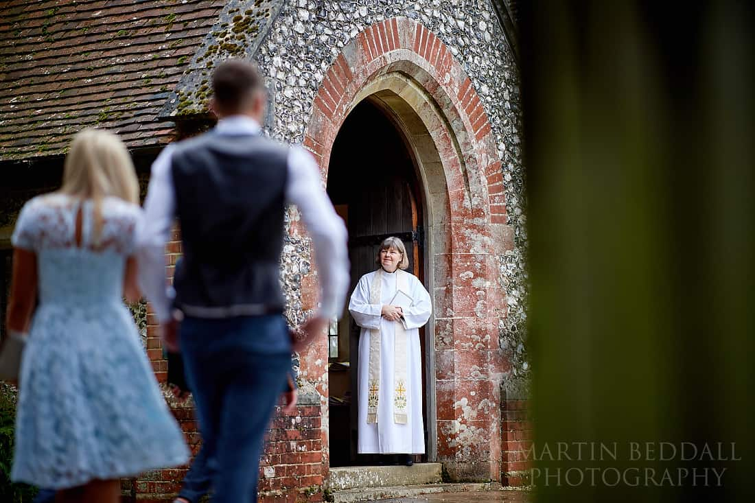 vicar waits at the church door