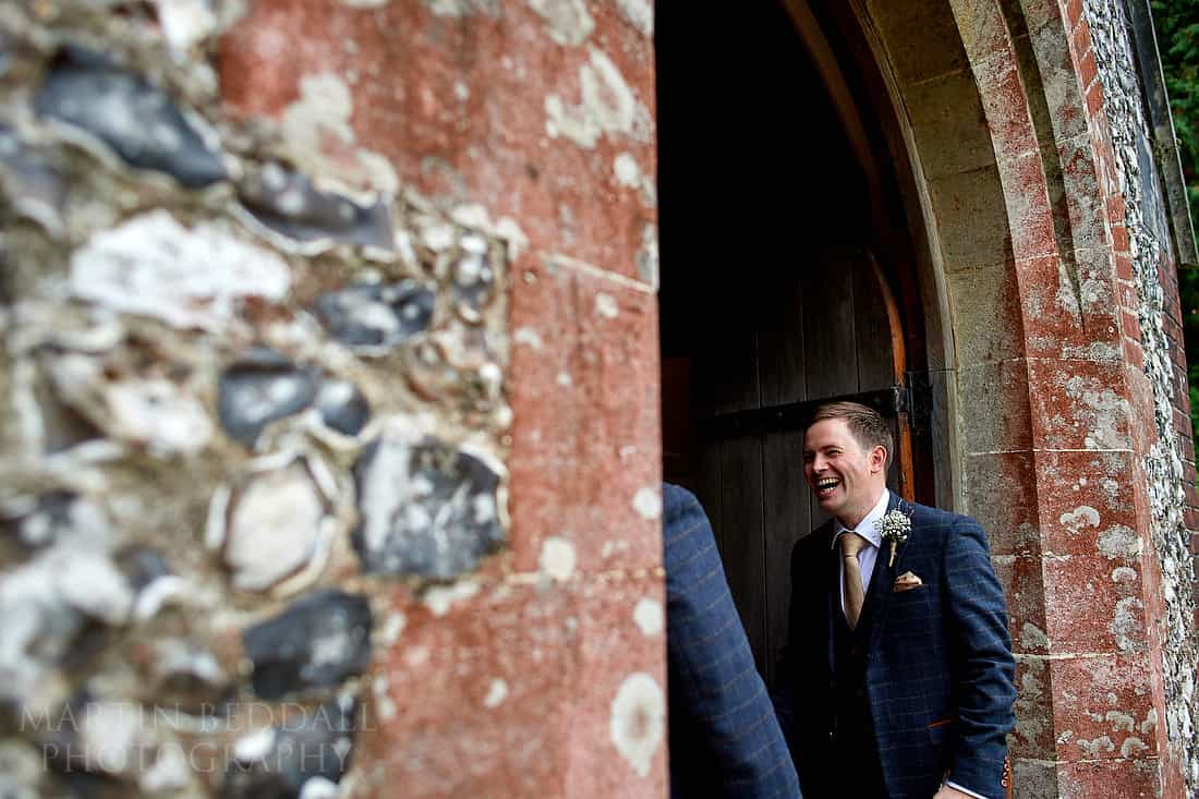 groom laughing at church door