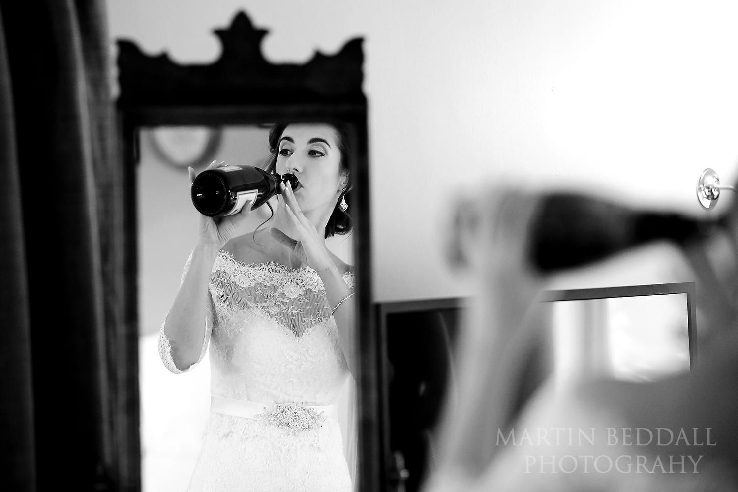 Bride takes a quick swig of champagne at Burley Manor wedding
