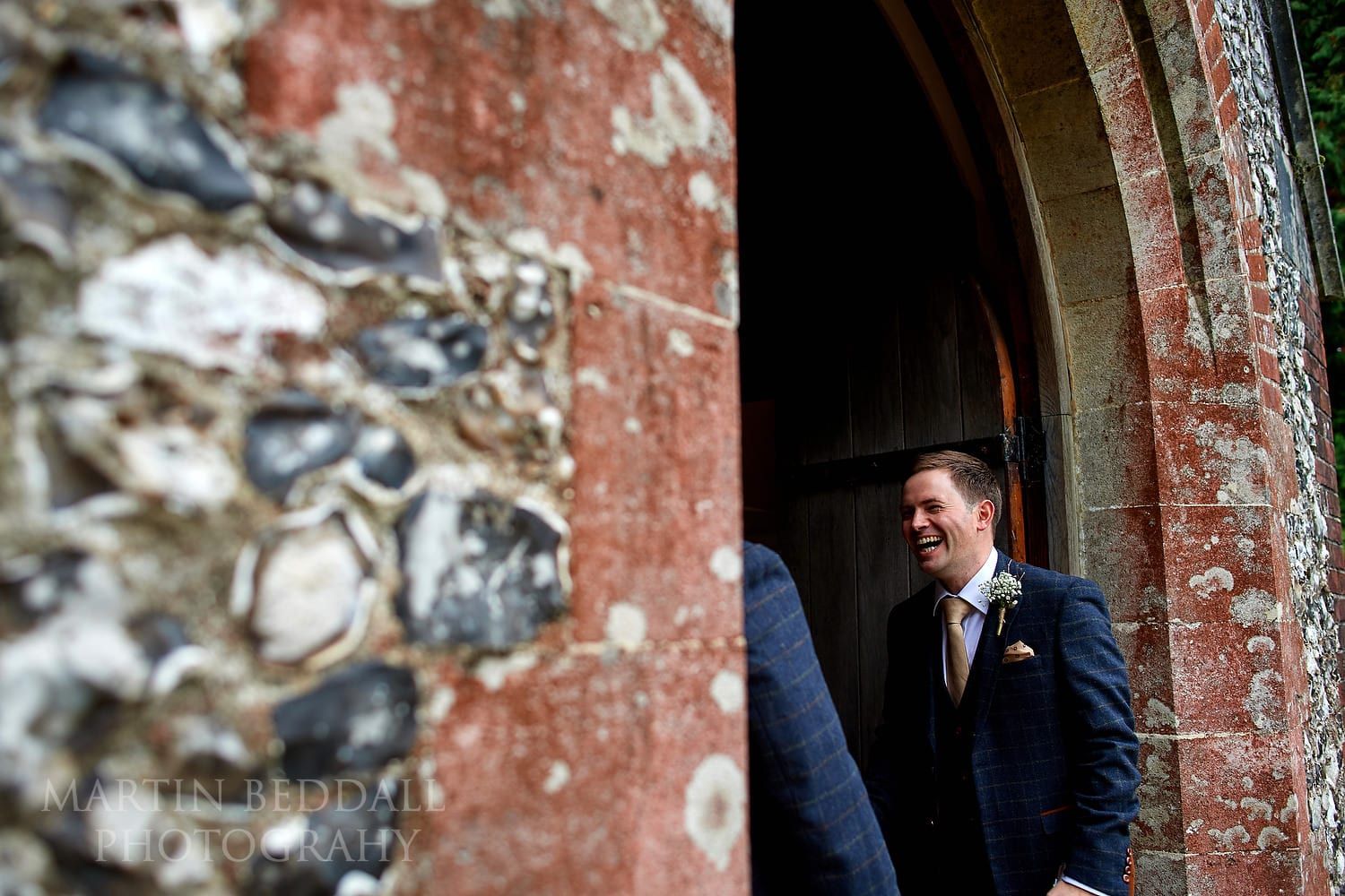 Groom laughing at Highclere church