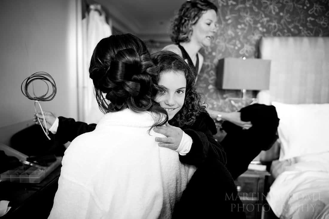 Flower girl hugs the bride