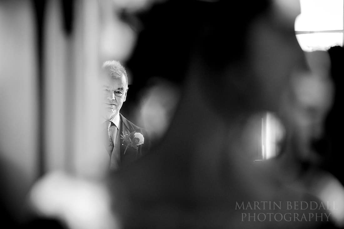 Father of the bride watches the bride get ready
