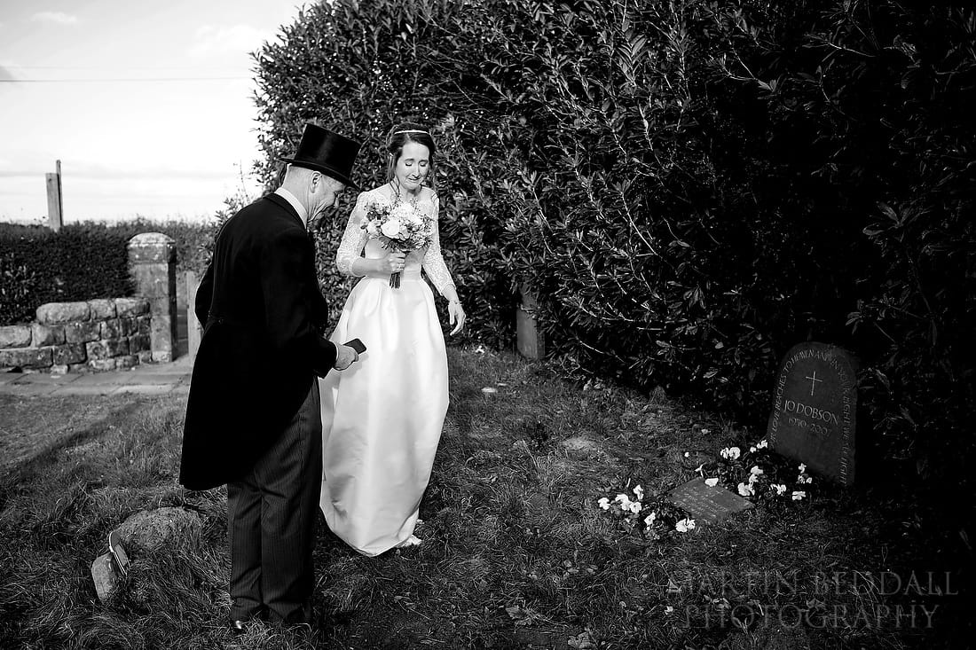 Tearful bride at her mother's grave