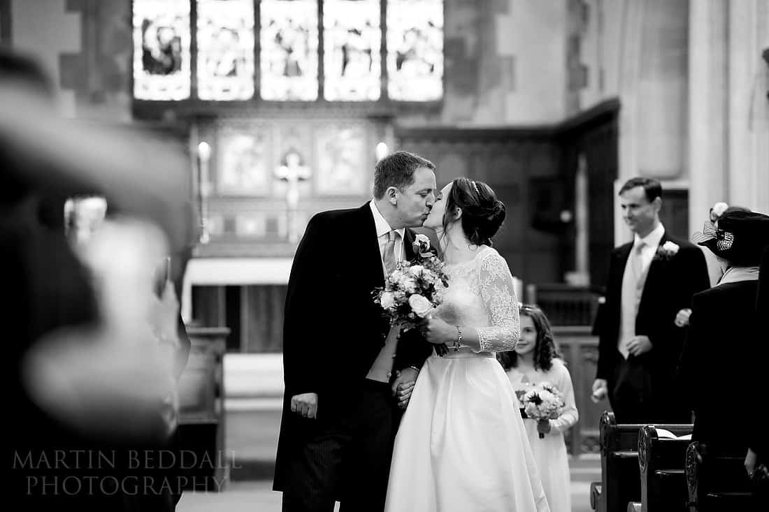 bride and groom kiss in the aisle
