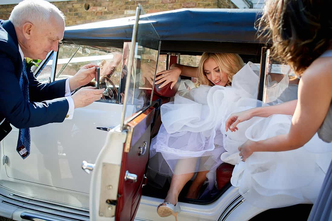 Bride squeezes out of the wedding car