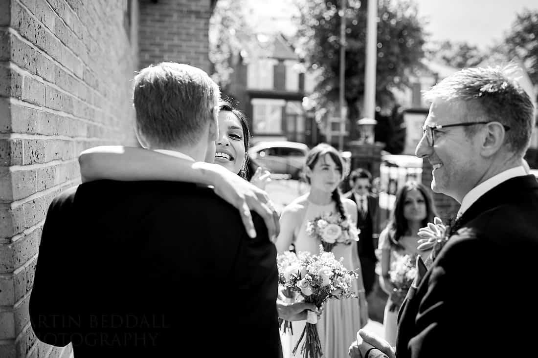 Bridesmaid hugs the groom