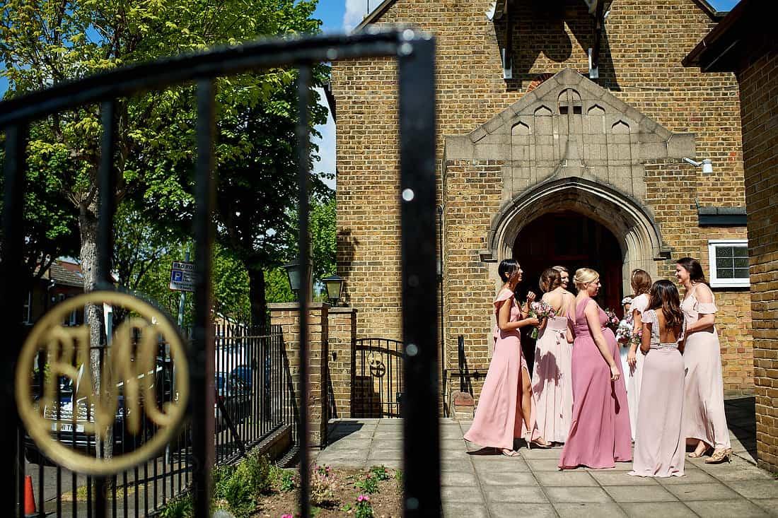 Bridesmaids wait outside the church
