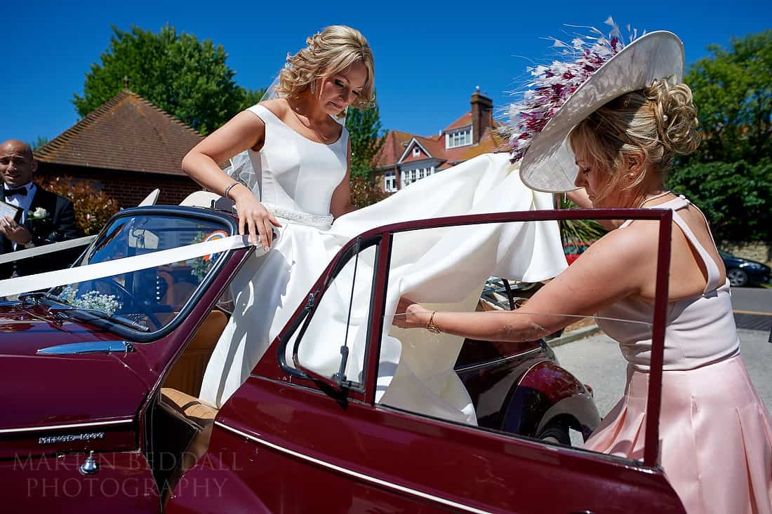 Bride helped out of the wedding car
