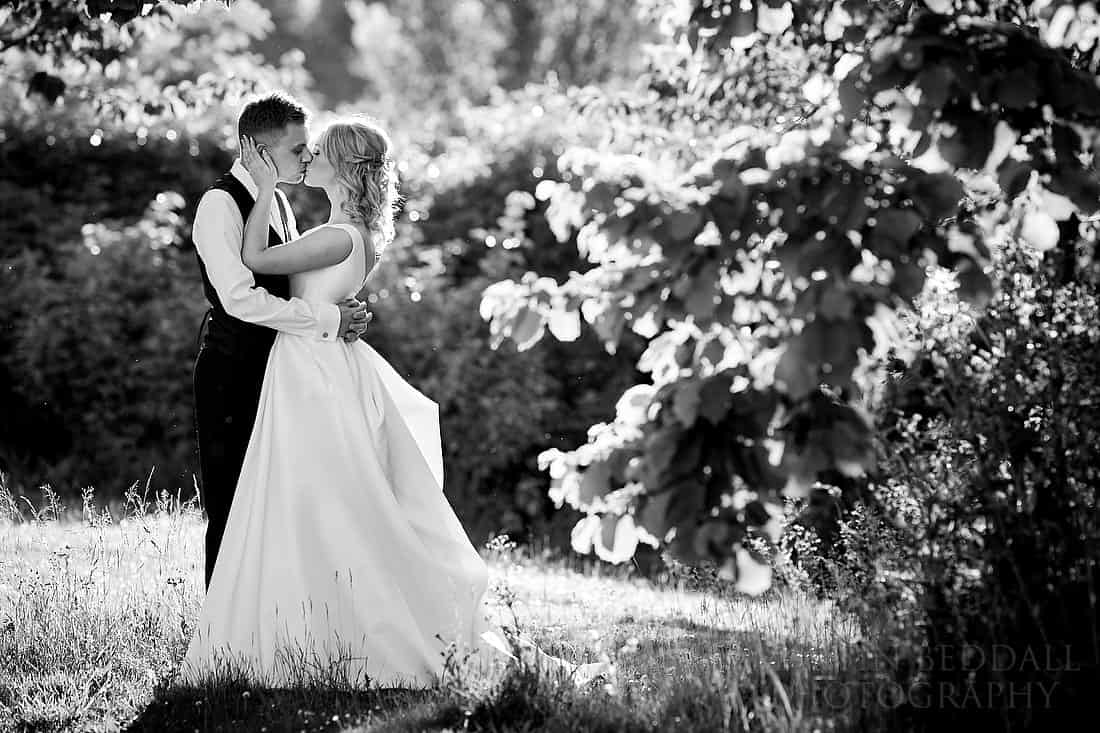 Bride and groom kiss in the park