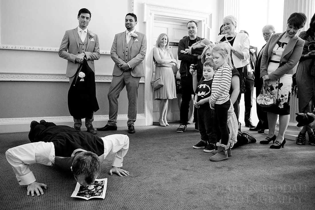 Groom performs pressups kissing a picture of the bride