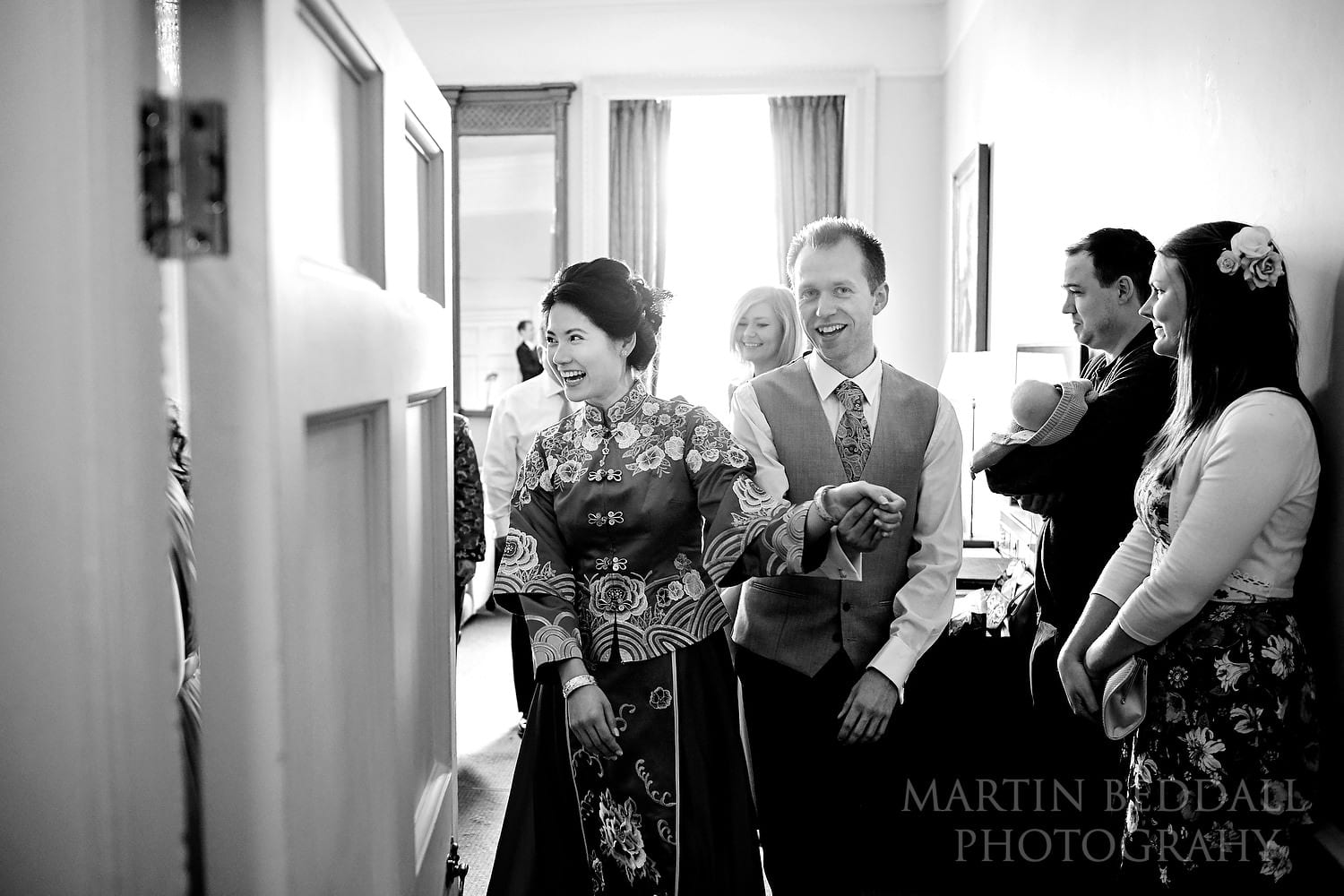 Groom escorts the bride to the Chinese tea ceremony at Buxted Park