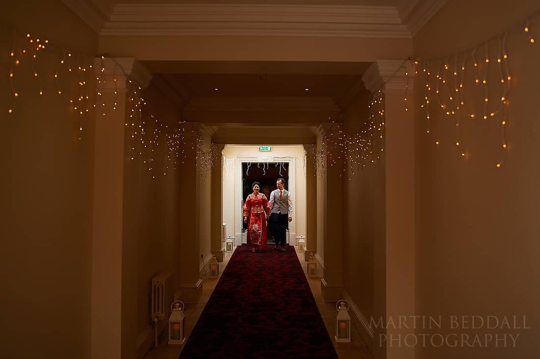 Groom escorts the bride down corridor