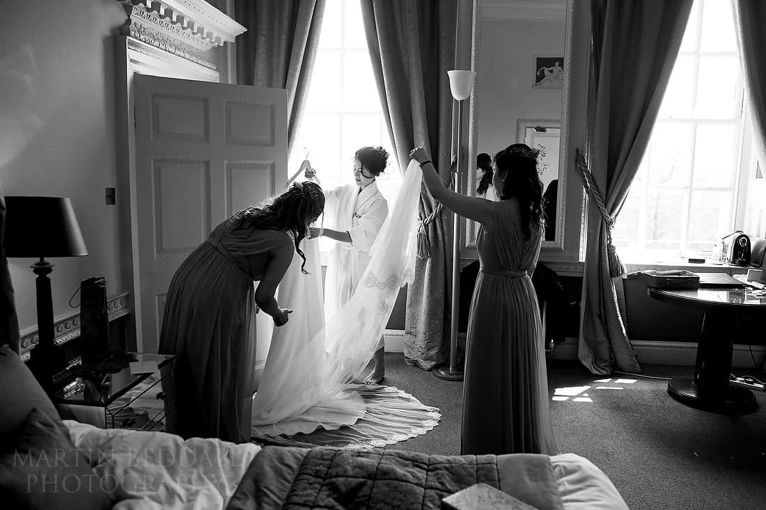 Bride and bridesmaids get the wedding dress ready