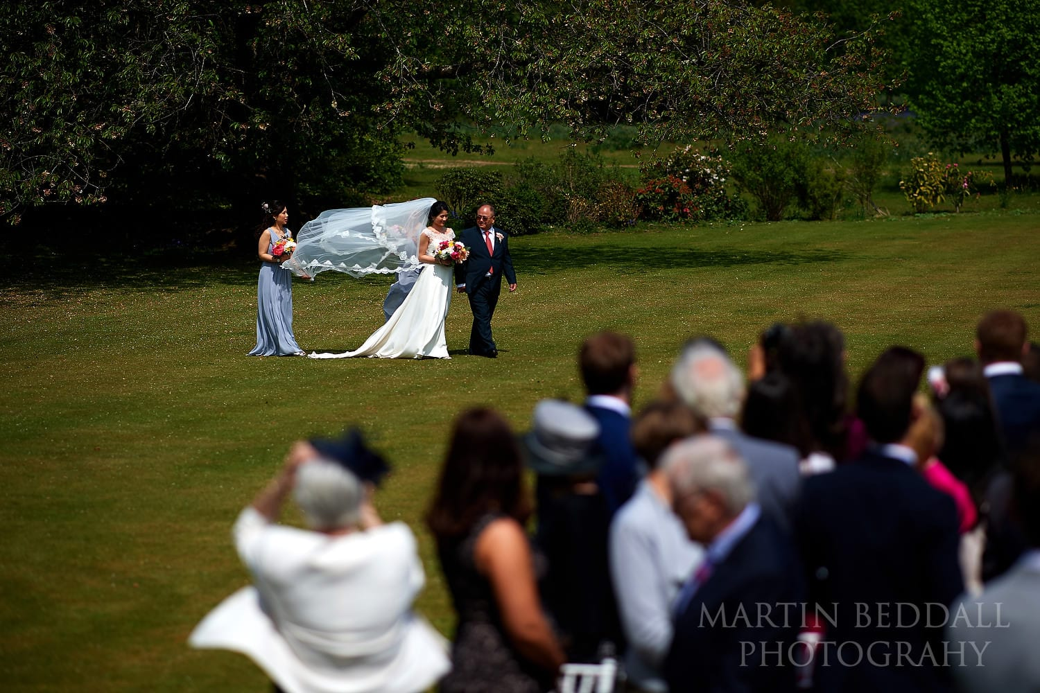 Bride walks towards the outdoor wedding ceremony at Buxted Park
