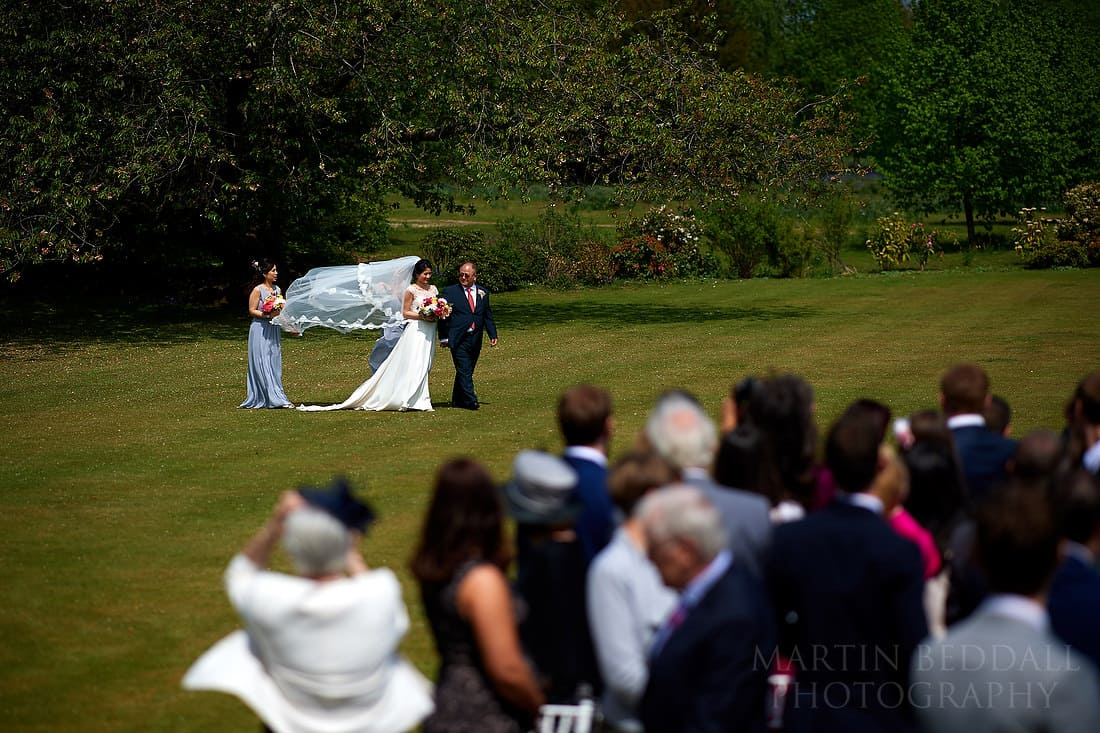 Bride walks across the lawn with her father