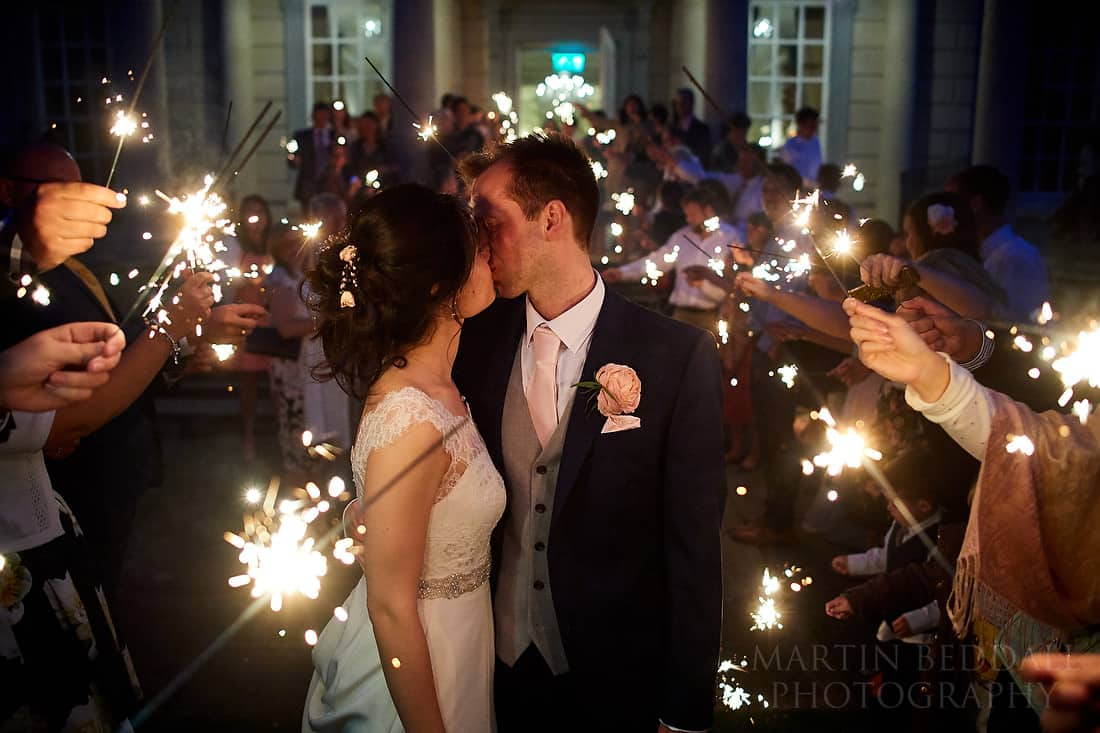 Bride and groom kiss amongst the wedding sparklers