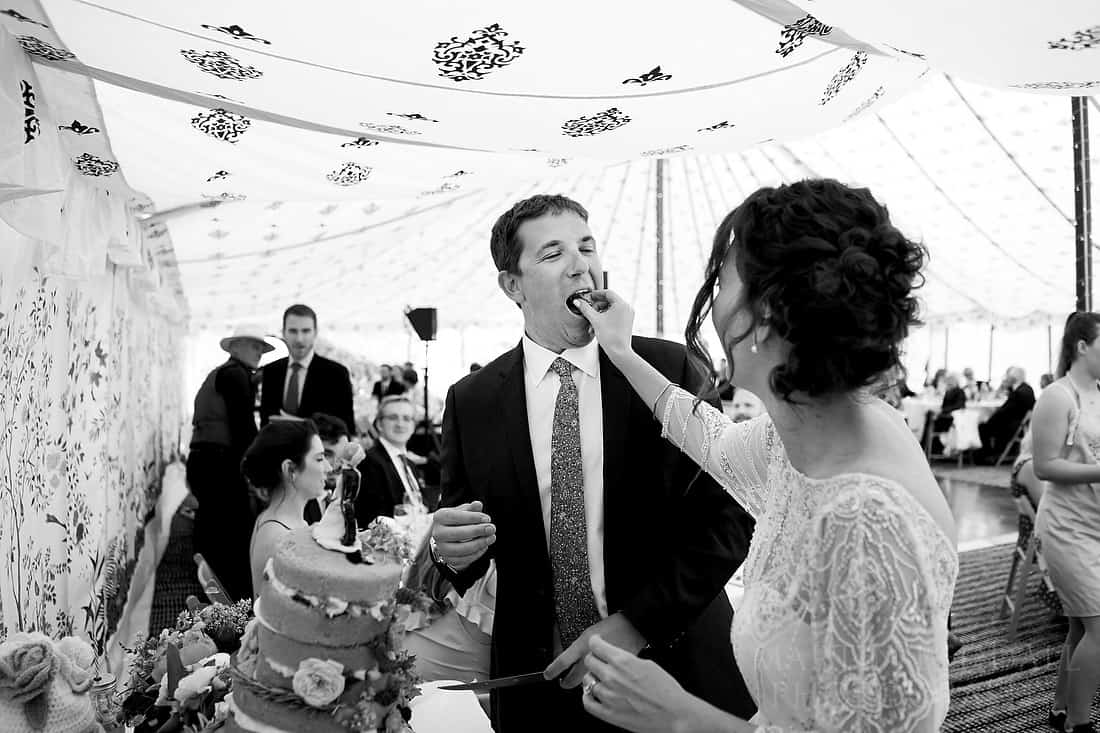 Bride feeds the groom wedding cake